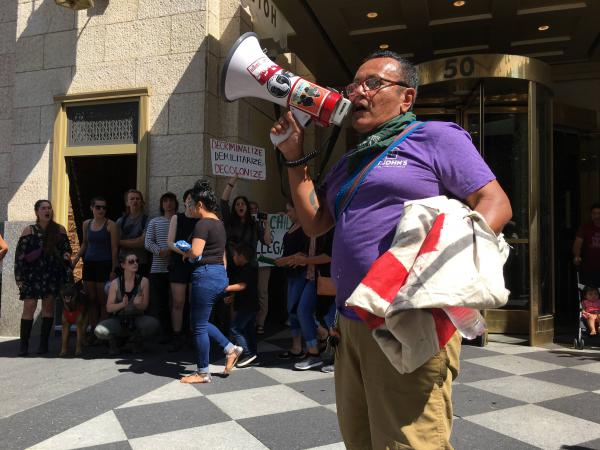Ruben Herrera leading chants with a bullhorn at an ICE protest in downtown Columbus.