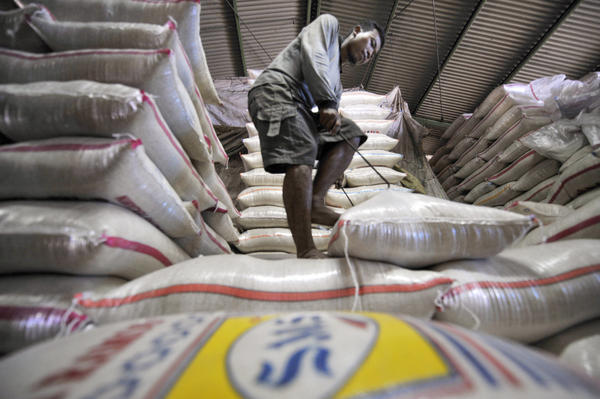 A laborer arranges sacks of rice at a market in Jakarta.