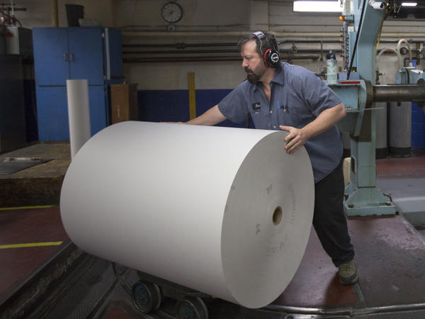 Jason Campbell adjusts rolls of newsprint before at <em>The Columbian</em> newspaper in Vancouver, Wash. The Trump administration launched a 22 percent tariff on imported newsprint from Canada, hitting U.S. newspapers with higher costs.