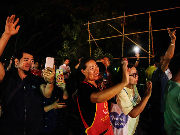 Onlookers in Chiang Rai, Thailand, watch and cheer as ambulances transport some of the rescued schoolboys from a cave where they were trapped for two weeks.