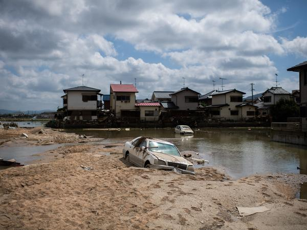 A damaged car is seen stuck in the mud in a flood-hit area in Mabi, in Japan's Okayama prefecture, on Tuesday.
