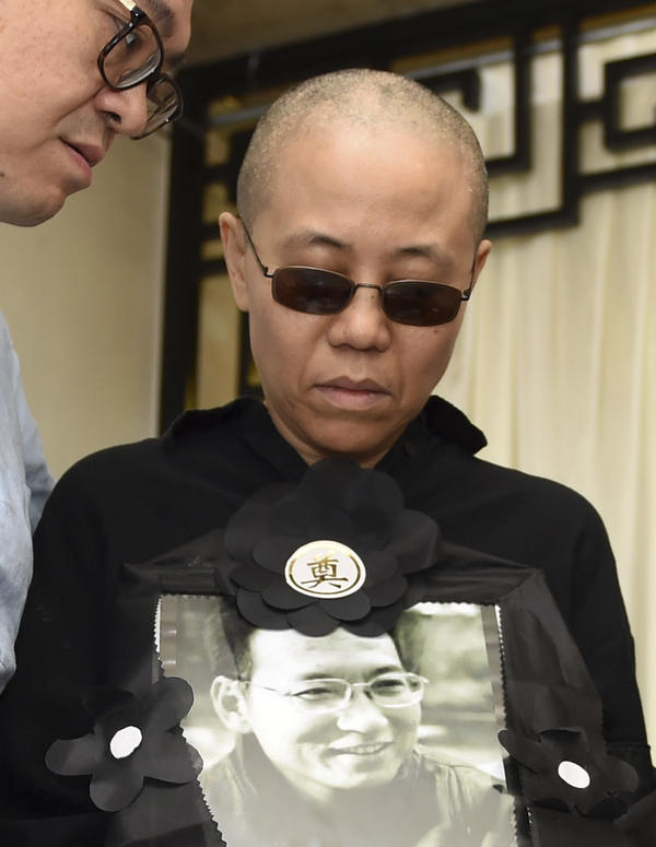 In a July 2017 photo released by the Shenyang Municipal Information Office, Liu Xia, wife of jailed Nobel Peace Prize winner and Chinese dissident Liu Xiaobo, holds a portrait of him during his funeral at a funeral parlor in Shenyang in northeastern China's Liaoning Province.