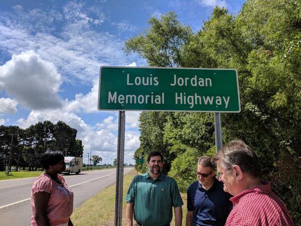 Arkansas Department of Transportation officials and other dignitaries after the unveiling of a sign Monday dedicating part of U.S. 49 between Brinkley and Marvel as the Louis Jordan Memorial Highway.