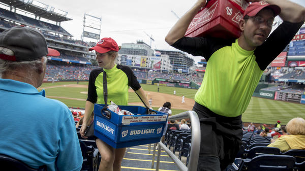 Nationals Park beer seller Christy Colt talks to customers as another beer seller passes in the stands during a recent Nationals game. She can carry up to 60 pounds of beer and ice at a time.