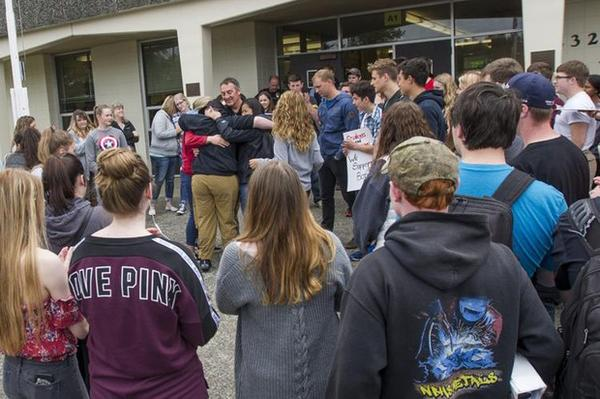 <p>A group of students embraces outgoing principal Bill Lucero during a walkout Wednesday morning at North Bend High School. Lucero was removed from his position by the school district in the wake of allegations of discrimination by a pair of students.</p>