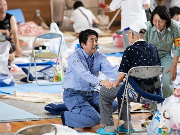 Japanese Prime Minister Shinzo Abe visits a shelter for people affected by the recent flooding in the Okayama prefecture on Wednesday.