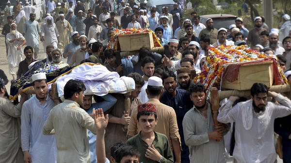 People carry the coffins of the victims of a suicide bombing at an election rally for burial in Peshawar, Pakistan, on Wednesday.