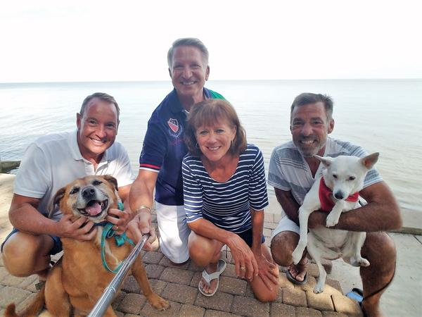 (l to r) Michael Meyer, Ruby, Bill Braunlich, Diane Thurber, Neal Thurber, and Ava. The next door neighbors have different approaches to keeping their dogs from being exposed to toxic cyanobacteria in Lake Erie.