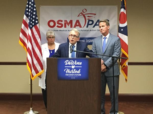 Mike DeWine (center) and Jon Husted talk about Medicaid expansion while they accept the endorsement of the Ohio State Medical Association.