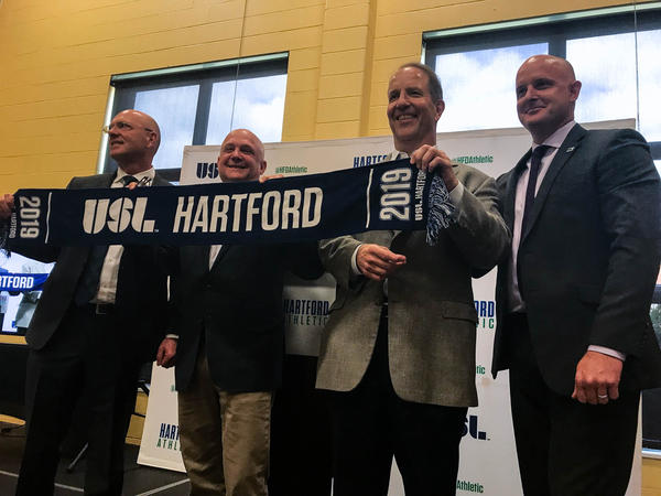 The team's co-owners (from left to right: Joe Calafiore, Bruce Mandell, and Scott Schooley) stand with United Soccer League president Jake Edwards (far right) in celebration of Hartford's new USL team.