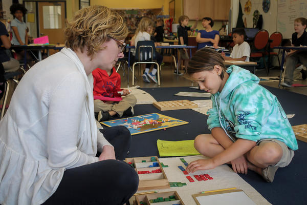 City Garden Montessori teacher Anne Lacey works with student Imani Palada, on math problems in April 2017.