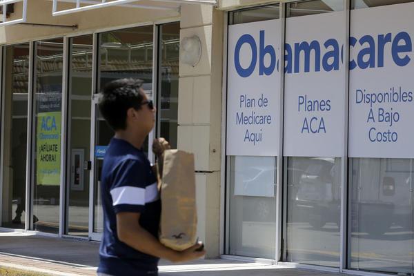 This photo taken Thursday, July 27, 2017, shows a man walks by an healthcare insurance office in Hialeah, Fla. (AP Photo/Alan Diaz)
