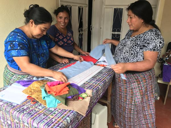 Mayan women in a Guatemalan village measuring and cutting fabric to be sewed into washable menstrual pads.
