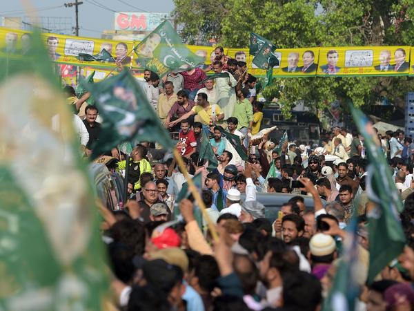 Supporters of ousted Pakistani Prime Minister Nawaz Sharif march toward Lahore's airport ahead of his arrival from London on Friday.