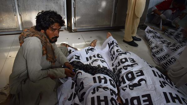 A man sits next to his relative's body Friday, shortly after bombing tore through a political rally in southwestern Pakistan.
