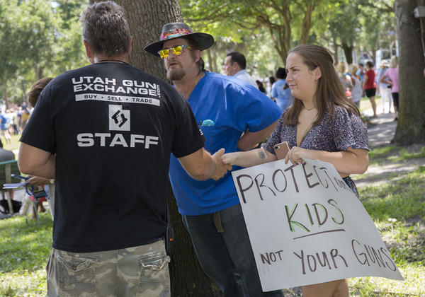 Members of the Utah Gun Exchange talk to pro-gun control activists at the St. Pete Road To Change event.
