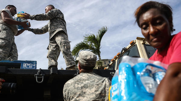U.S. Army soldiers pass out water, provided by FEMA, to residents in a neighborhood without grid electricity or running water on Oct. 17, 2017 in San Isidro, Puerto Rico.