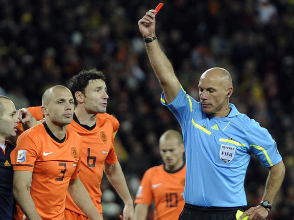 Referee Howard Webb of England, right, shows the red card to Netherlands' John Heitinga, left, during the World Cup final soccer match between the Netherlands and Spain at Soccer City in Johannesburg, South Africa, Sunday, July 11, 2010.