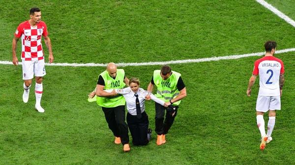 An intruder, identified as a member of the Russian collective and punk band Pussy Riot, is carried off the pitch during the 2018 World Cup final game between France and Croatia on Sunday.