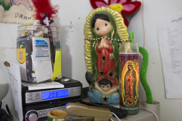 A small shrine to the Virgin of Guadalupe sits behind the counter at the <em>tienda</em> that Fabiola Escamilla owns in Galax, Va. Escamilla is a DACA recipient. Despite living in Galax for much of her life and raising her two sons there, she is still very concerned about her immigration status.