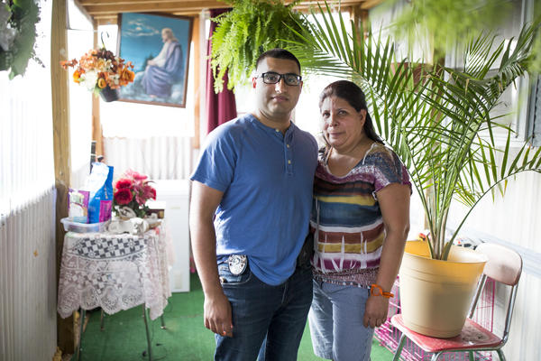Officer Eduardo Mata, left, stands with his mother Leticia Mata, right, on the porch of the trailer they share in Galax, Va. Mata graduated from the police academy on June 28. He is one of only two Spanish-speaking officers. Mata grew up in the Hispanic community in Galax and says that many residents were afraid of encounters with police.