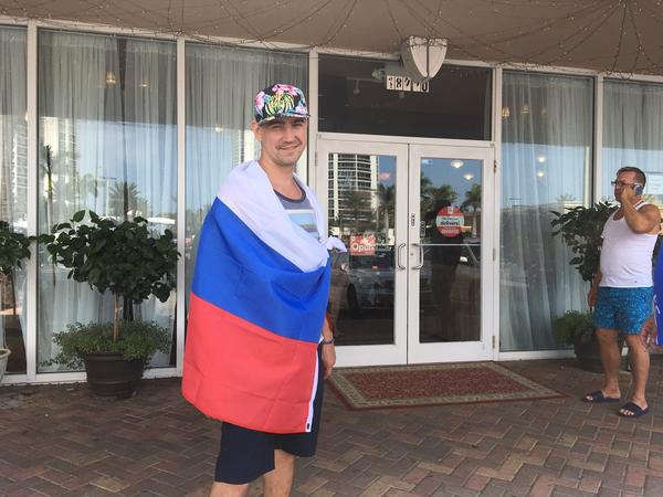 Constantine Orain, draped in the Russian Federation flag, standing outside Old Samovar restaurant in Sunny Isles.