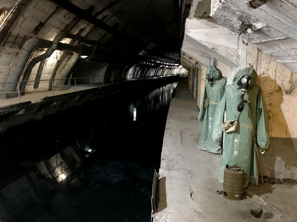 Hazmat suits hang next to the canal that leads from Balaklava Bay to the heart of the underground base.