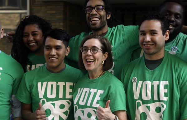 """<p>Oregon Democratic Gov. Kate Brown, middle, poses for photos with student volunteers during a """"get out the vote"""" gathering at Portland State University on Oregon's primary election day Tuesday, May 15, 2018, in Portland, Oregon. Brown's campaign is coordinating with a union-funded group called Defending Oregon's Values to run ads against her Republican challenger, Oregon state Rep. Knute Buehler.</p>"""