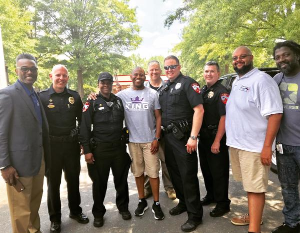 Tru Pettigrew and Chief Tony Godwin in the center, surrounded by other police officers and members of the community.