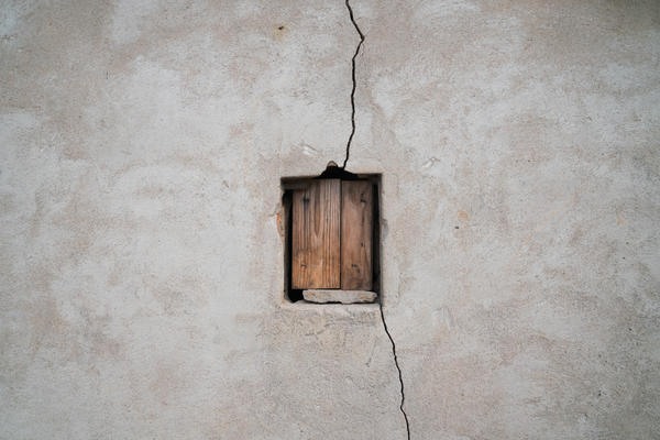 A small window on Machinga's shed is boarded up and a crack runs through the wall. Machinga has been rebuilding her house on her own, bit by bit, on the same spot, living among the same people who burned it down.