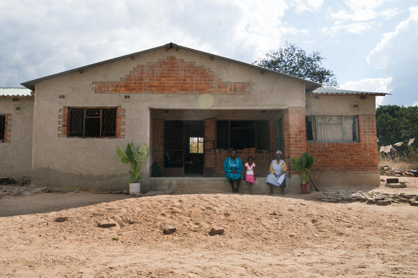 Florence Machinga with her daughter Hazel and mother Rosemary at the home they are slowly rebuilding after it was destroyed in 2008.