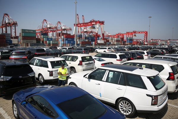 A worker inspects imported cars at a port in Qingdao, Shandong province, China on May 23.