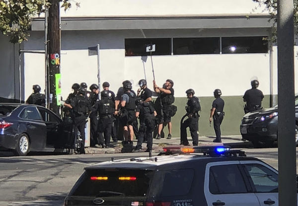 Police officers use a mirror to see inside a Trader Joe's store in the Silver Lake neighborhood of Los Angeles on Saturday. Los Angeles police say 28-year-old Gene Evin Atkins took hostages in a three-hour standoff at the store.