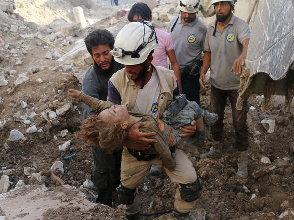 A Syrian Civil Defense volunteer, known as the White Helmets, holds the body of a child after he was pulled from the rubble following a government forces airstrike on the rebel-held neighborhood of Karm Homad in the northern city of Aleppo on Oct. 4, 2016.