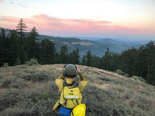 <p>A wildland firefighter looks out over one of the fires burning in the Southern Oregon Garner Complex Saturday, July 21, 2018.</p>