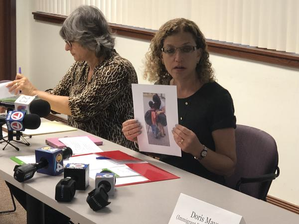 Wasserman Schultz holds up a photo of an immigrant mom being reunited with her two sons in Florida. She met the mom before the discussion on Friday but did not use her name in order to protect her privacy.
