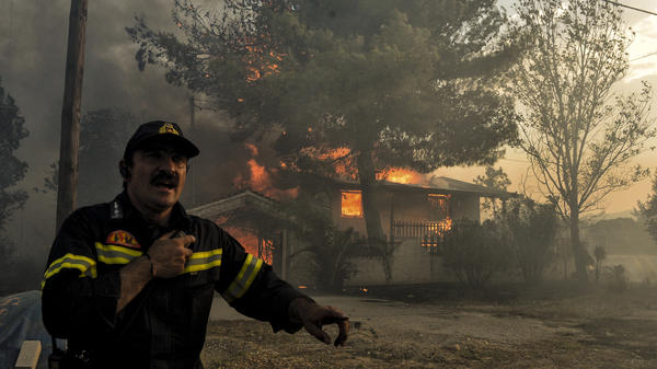 A firefighter next to a house burning during a wildfire in Kineta, near Athens, Greece, on Monday. Wildfires are not new to Greece but several blazes erupted especially quickly.