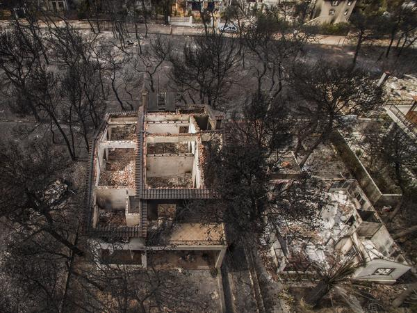 Wildfires left behind burned-out shells of homes in the village of Mati, near Athens. Greek Red Cross workers discovered 26 bodies in the devastated resort village.