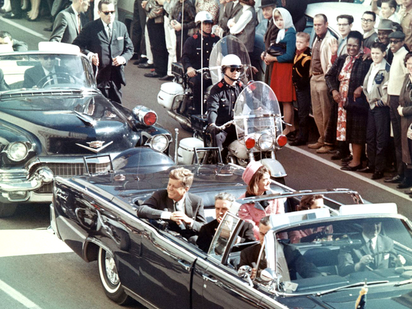President John F. Kennedy riding down main sreet in Dallas, Texas, minutes before he was assasinated. He is accompanied by his wife, Jackie Kennedy, as well as Texas Governor John Connally and his wife, Nellie.