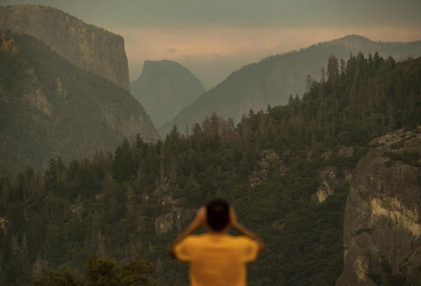 A visitor photographs Half Dome on Tuesday as smoke from the Ferguson Fire is visible in Yosemite National Park, a day before authorities closed parts of it.