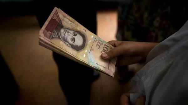 A Venezuelan holds a stack of near-worthless 100 bolivar bills at a shop in Caracas this year.