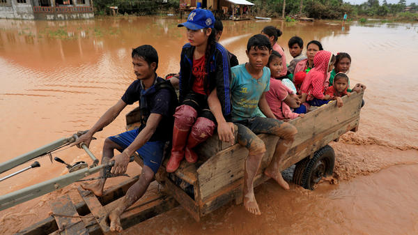 Children and a woman sit on a locally made vehicle in Laos as they travel during flooding caused by the collapse of a dam in the Xe Pian-Xe Namnoy hydroelectric project in Attapeu Province.