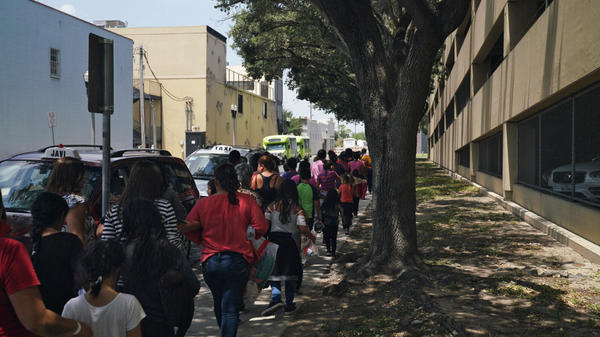 Women and children walk to a bus in McAllen, Texas. People released from immigration detention centers are often dropped off at the McAllen bus station nearby.