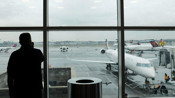 A passenger looks over planes sitting on the tarmac at LaGuardia Airport in New York City on Nov. 22. A previously undisclosed TSA program flags passengers for observation, and undercover air marshals observe their behavior — including whether they make calls or send texts as they travel, <em>The Boston Globe</em> reports.