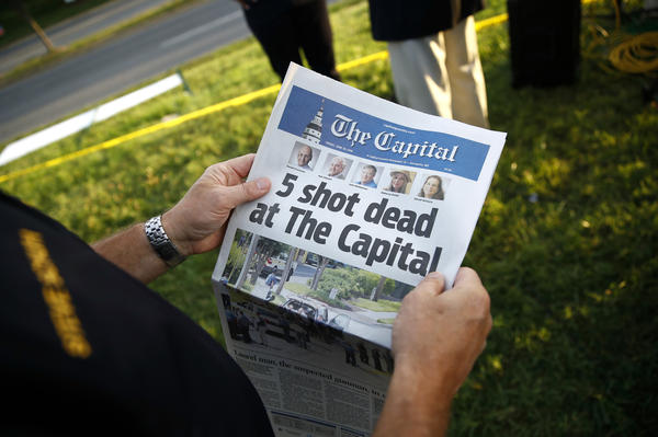 Steve Schuh, county executive of Anne Arundel County, holds a copy of <em>The Capital</em> newspaper last month near the scene of a shooting at the Capital Gazette newsroom in Annapolis, Md.