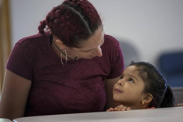 Genie Garda, and her 4-year-old daughter, Getzaynoe Hernandez, sit at a table at a potluck dinner in Dracut for women who evacuated from Puerto Rico. (Jesse Costa/WBUR)
