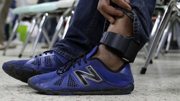 An immigrant wears an ankle monitor as he sits at a shelter in McAllen, Texas after he was released after processing by U.S. Customs and Border Protection.