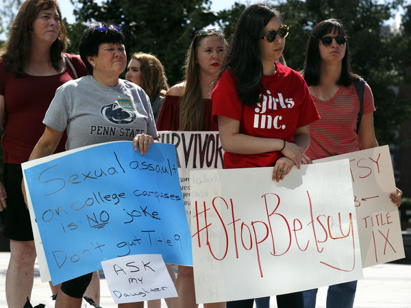 "Sonja Breda, 23, (right) sends a message to Education Secretary Betsy DeVos with a ""Stop Betsy"" sign as survivors of sexual violence and their supporters protest before DeVos spoke in September 2017 at the George Mason University's Arlington, Va., campus."