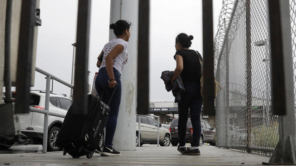 Sisters from Guatemala seeking asylum, cross a bridge to a port of entry in to the United States from Matamoros, Mexico, in Brownsville, Texas.