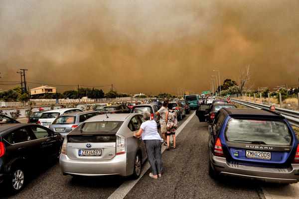 Cars are blocked at the closed National Road as a wildfire rages in Kineta, west of Athens.